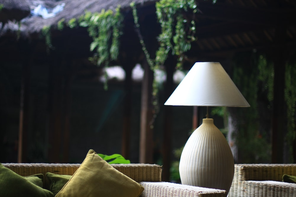 turned-off white table lamp near brown wicker chair