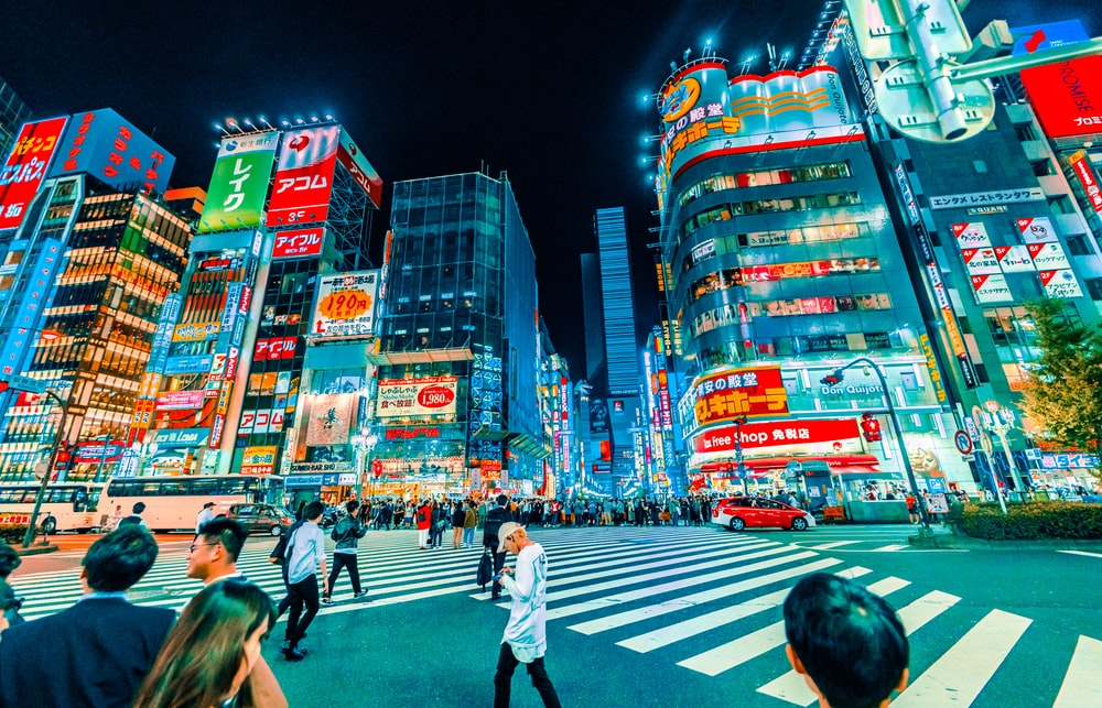 people crossing pedestrian near buildings at night