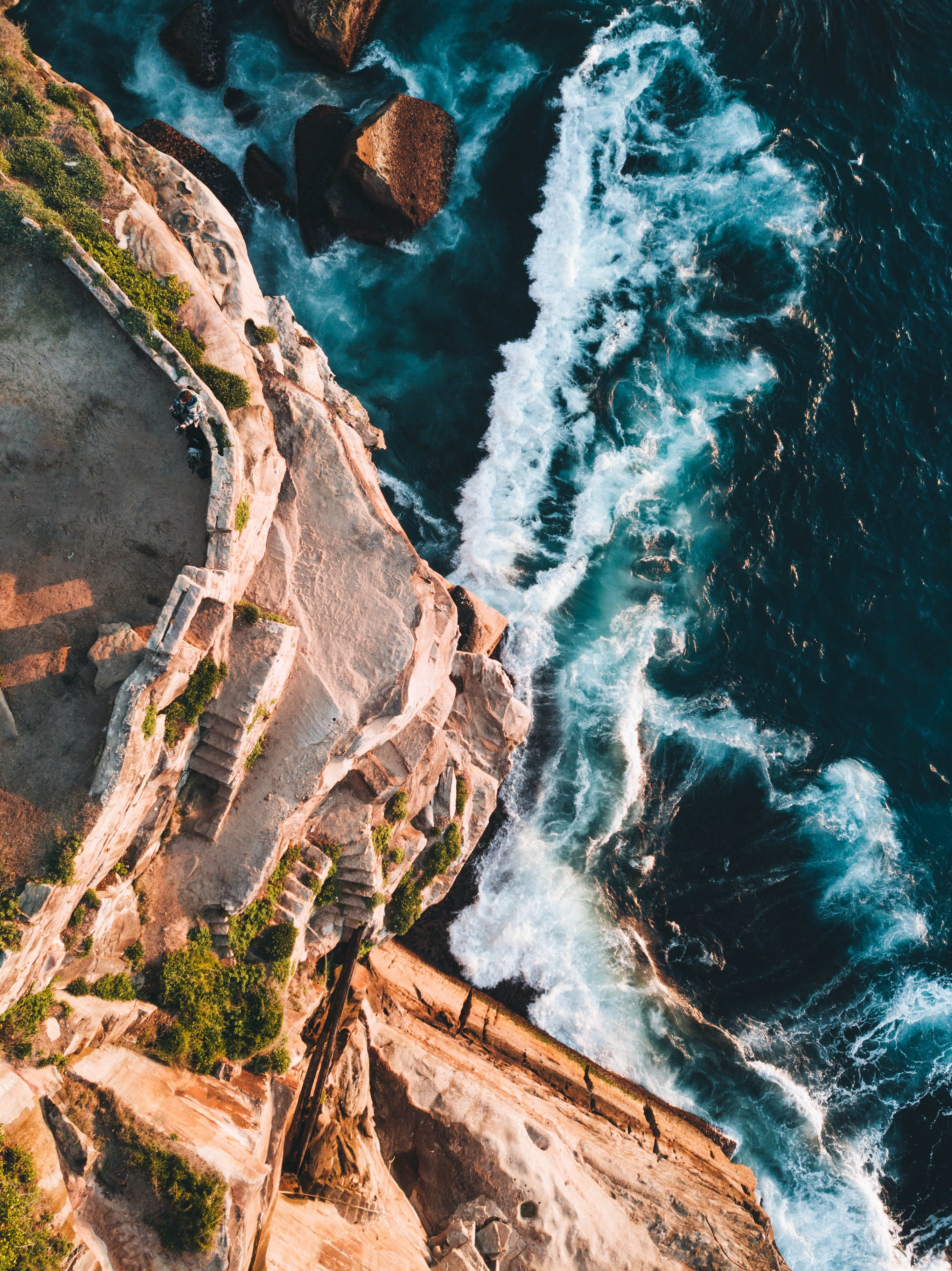 bird's eye view photography of cliff and sea waves