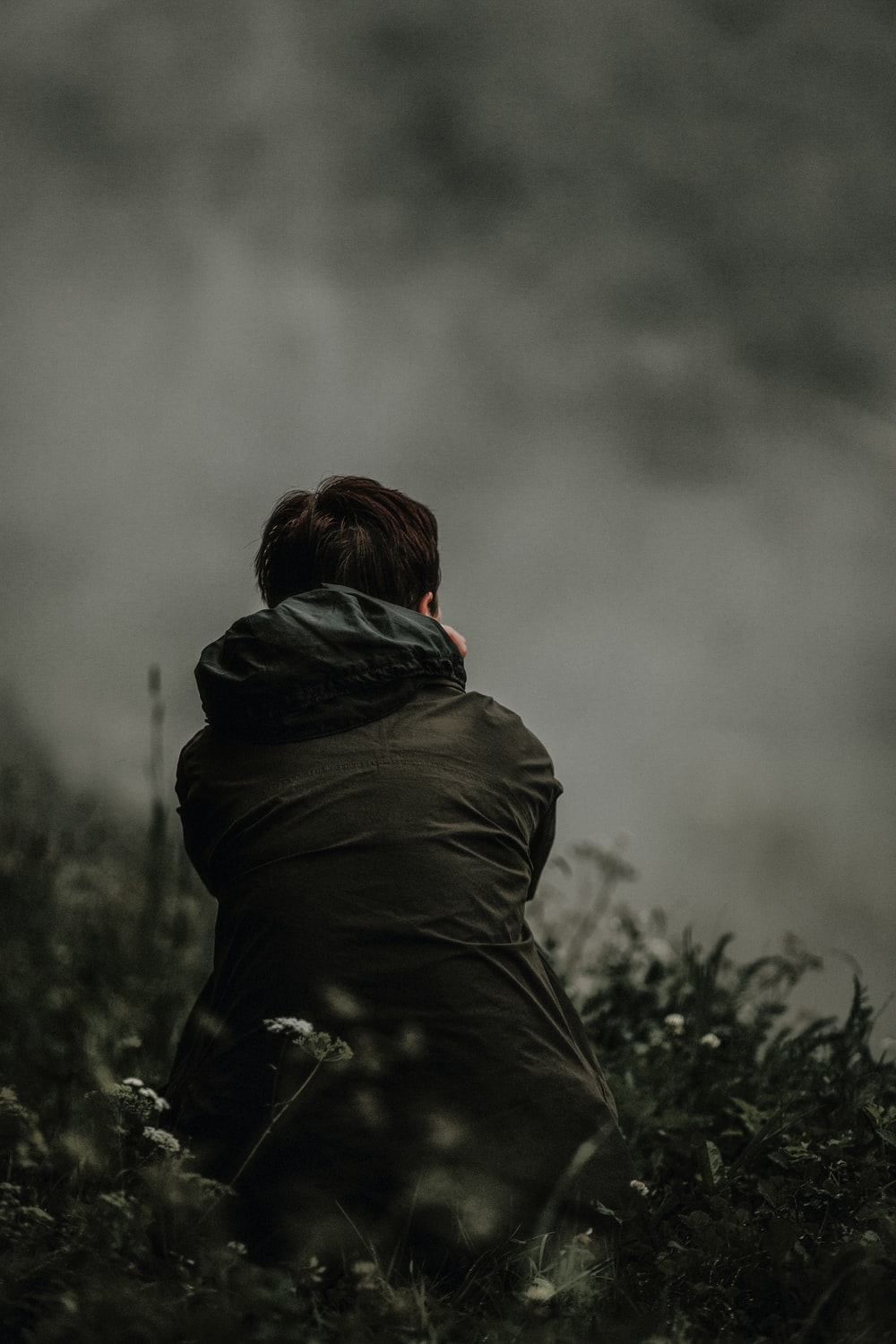 selective focus photo of person in black hooded jacket sitting on green grass field at daytime