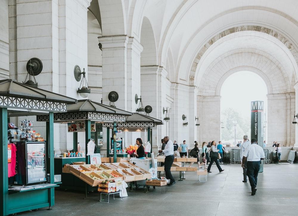 people walking under white concrete building
