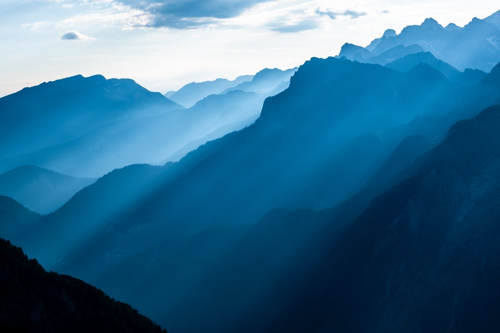 landscape photography of mountains while rays passing through it