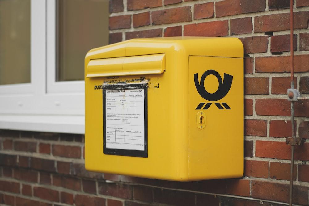 yellow mailbox on brown wall bricks