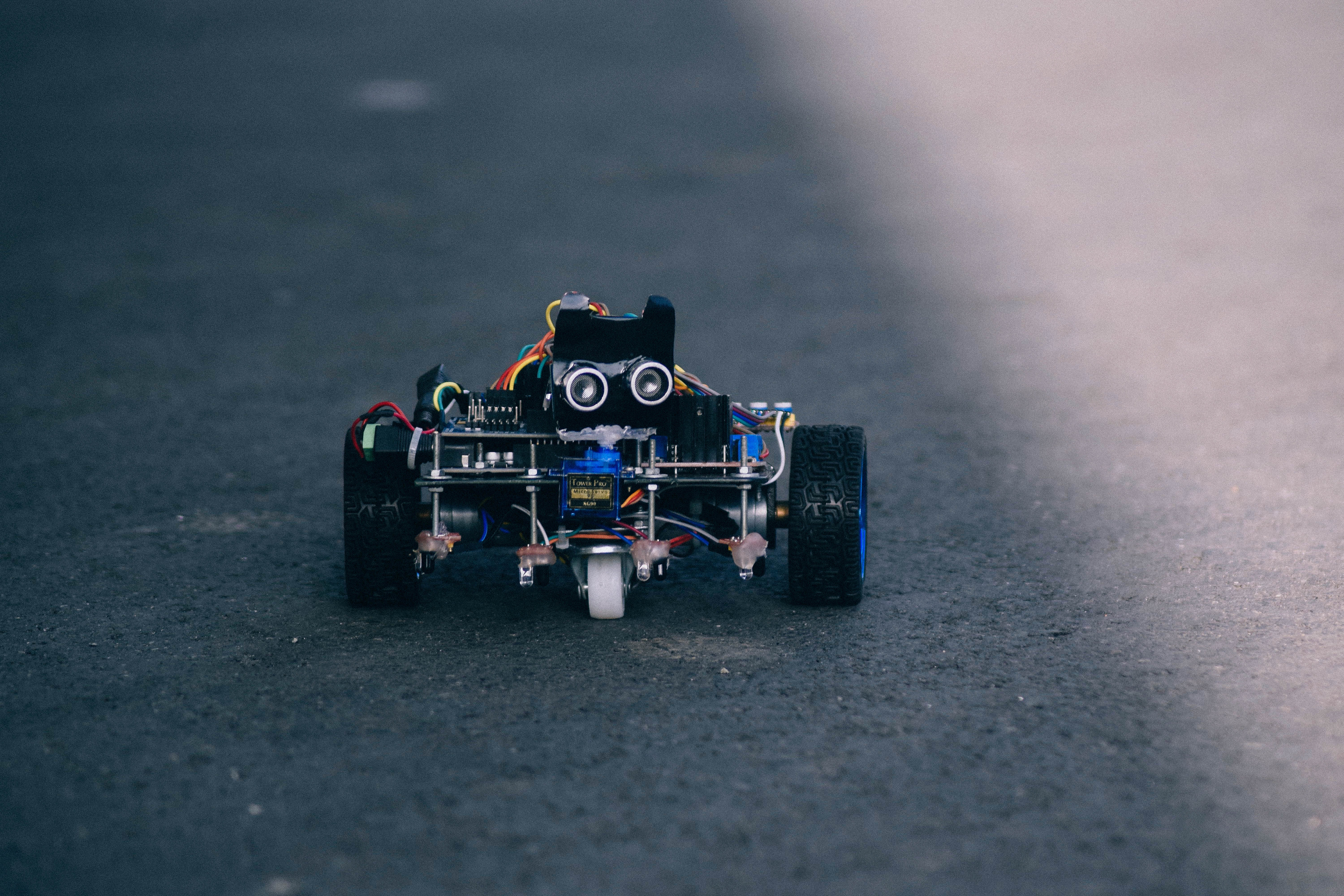 black and blue RC car on gray pavement