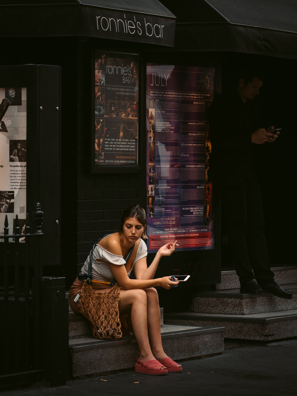 woman holding smartphone sitting on Ronnie's Bar store