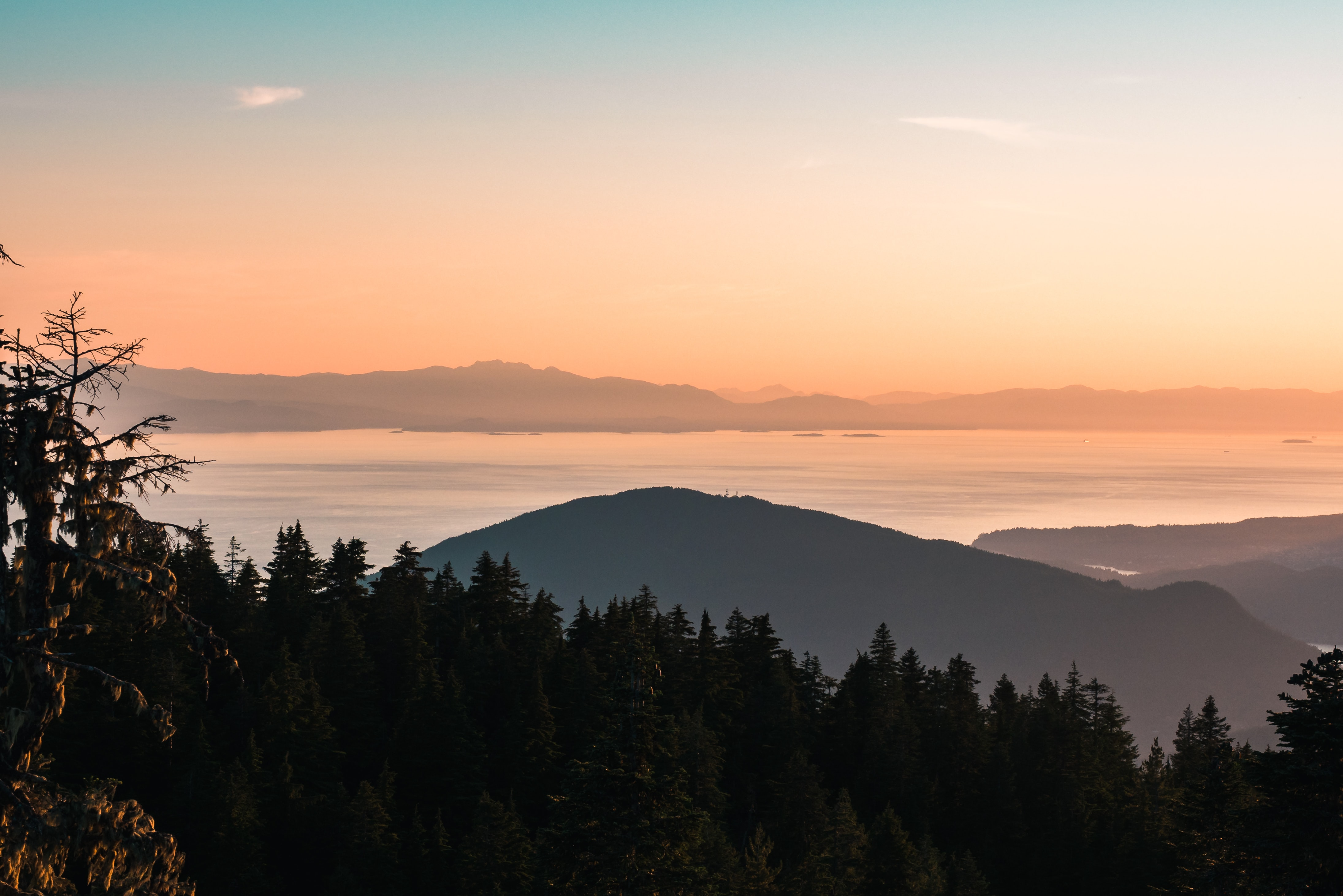 photo of mountain, body of water, and forest during sunset