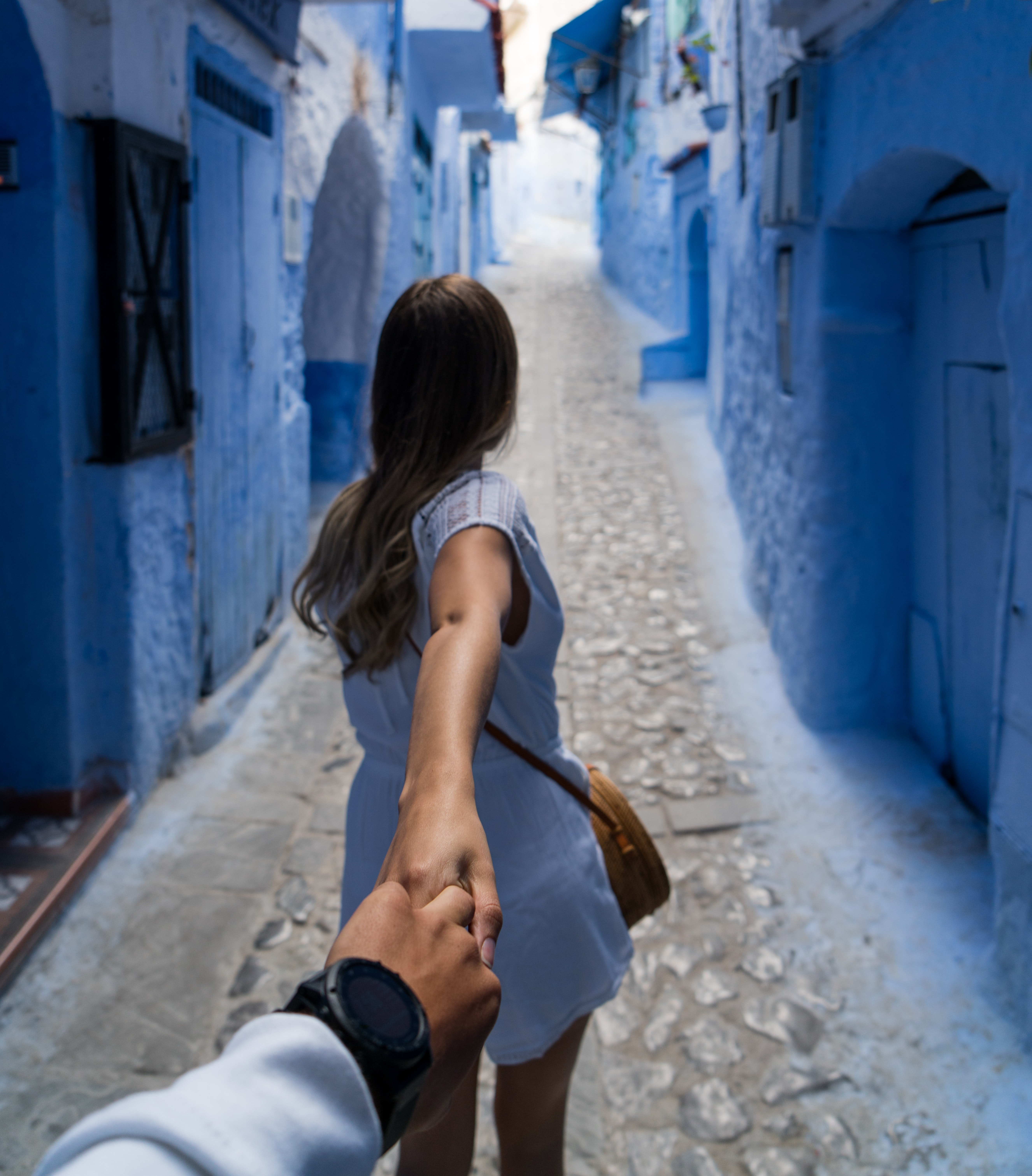 woman holding man's hand while walking on alley