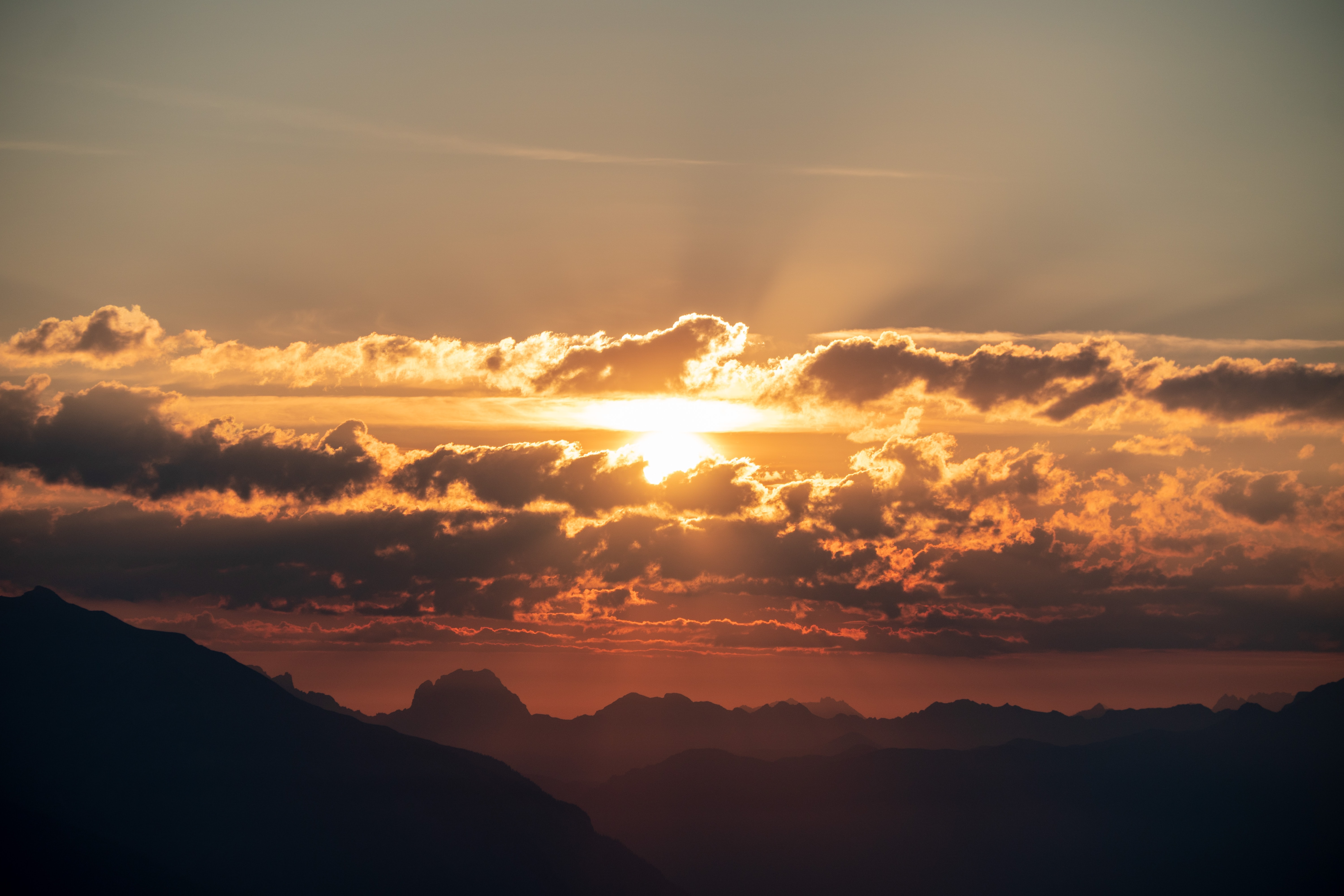 mountains under orange sky with sun rays piercing through clouds