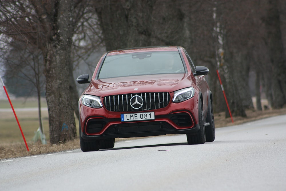 red Mercedes-Benz vehicle on roadway near trees