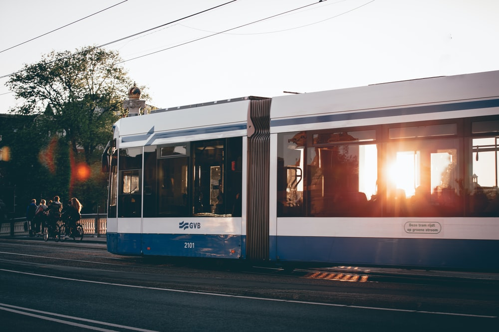 person taking photo of white-and-blue train wagons