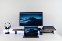 black laptop computer under black flat screen TV