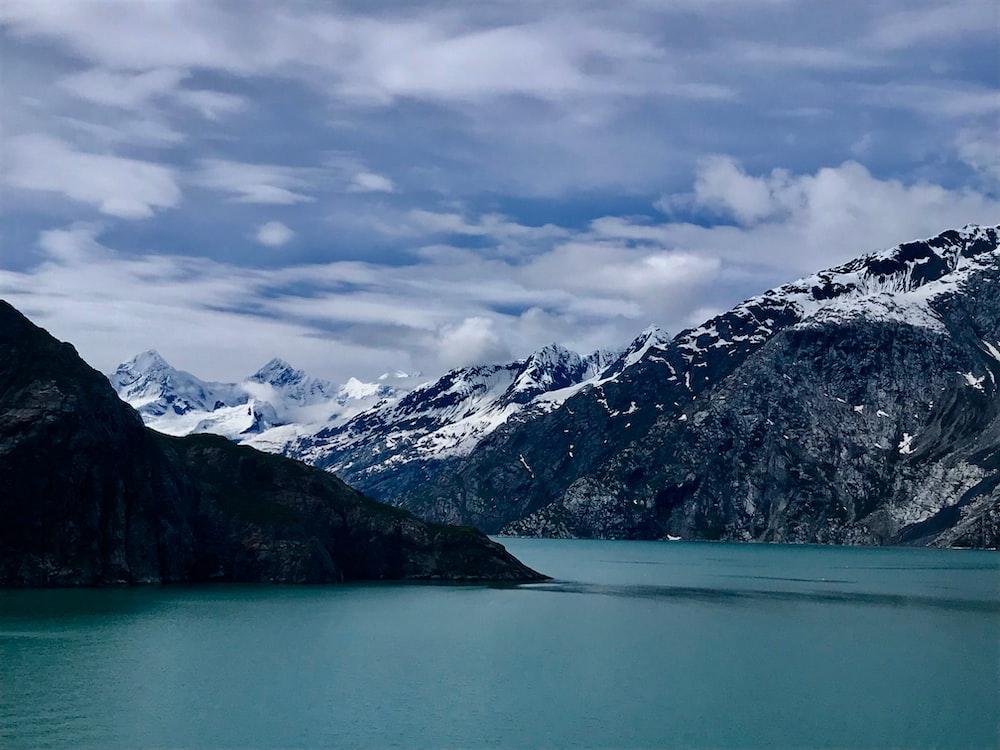 calm lake near glacier mountain during daytime