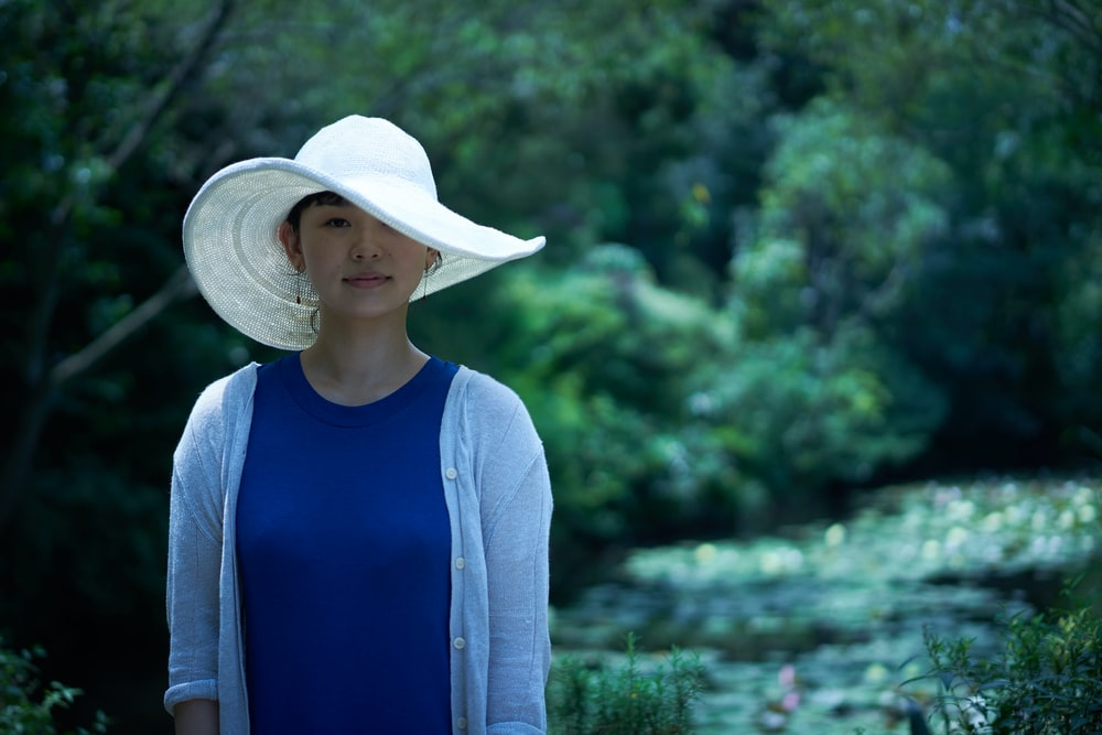 woman wearing sun hat and cardigan