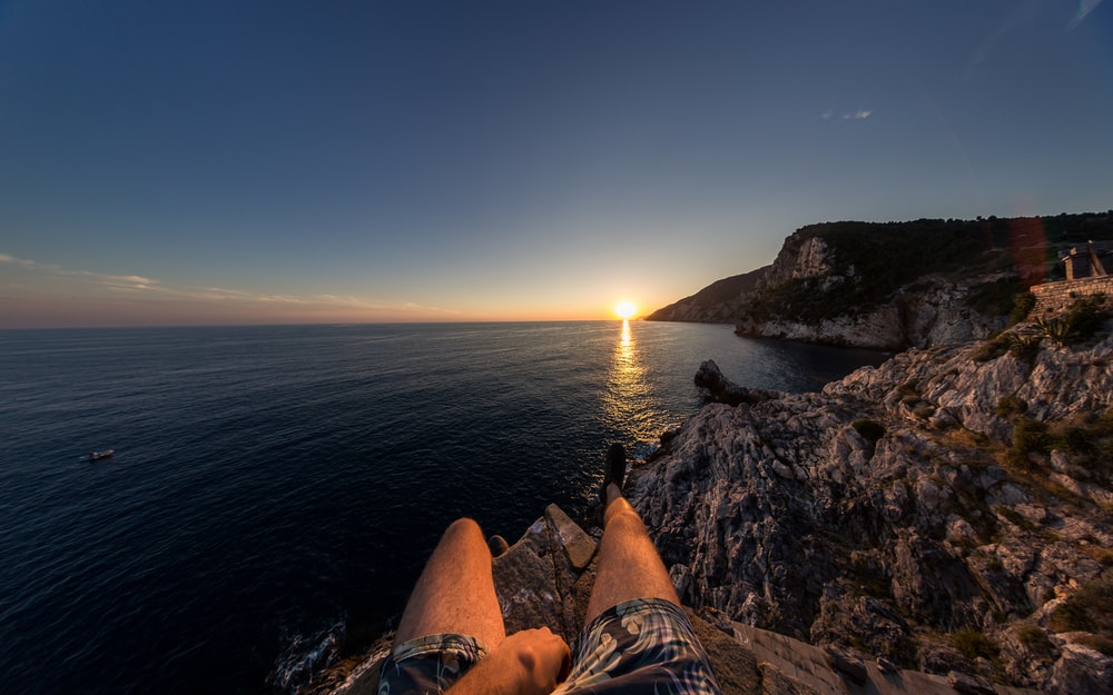 person sitting on cliff in front of sea