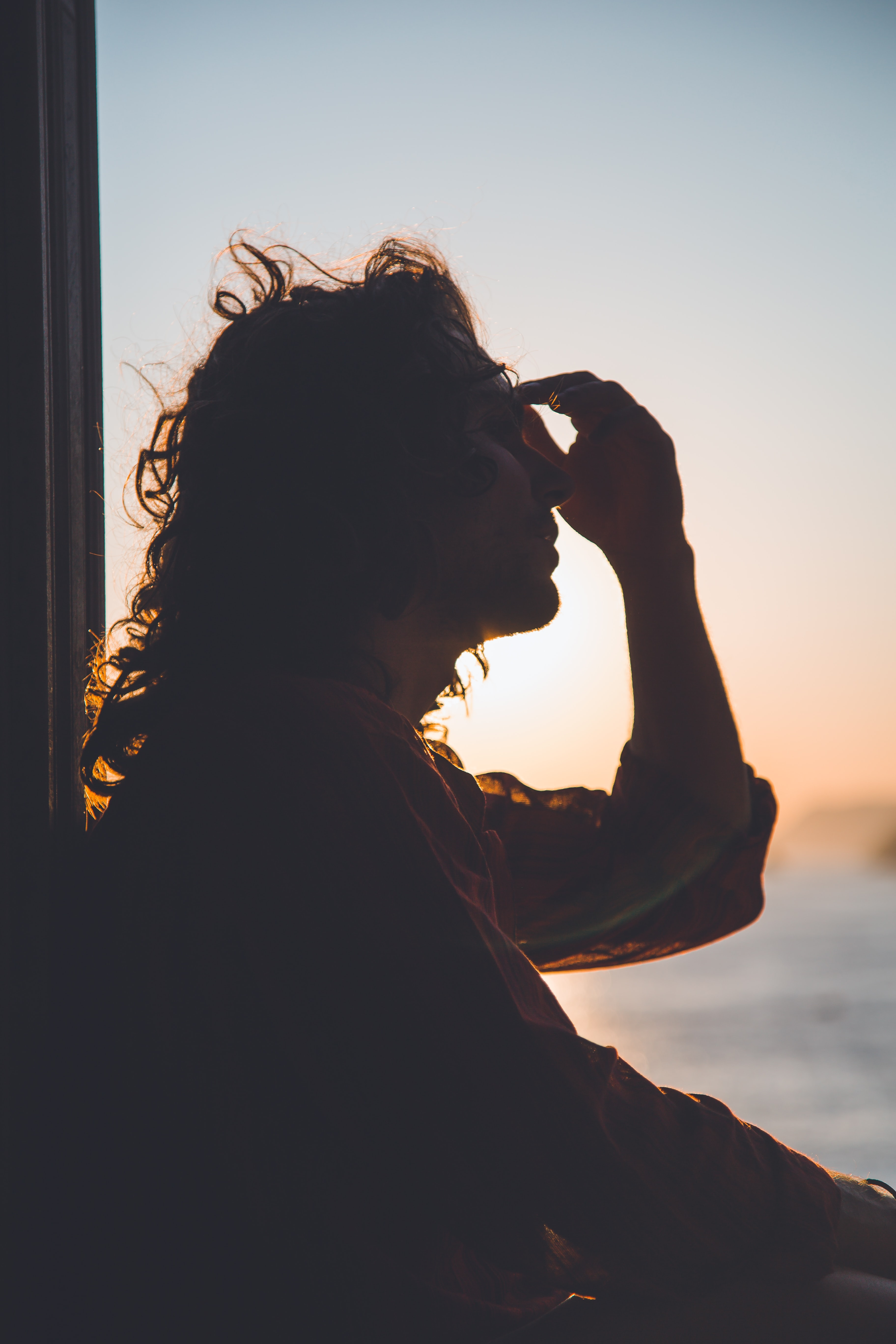 man holding forehead under sunset