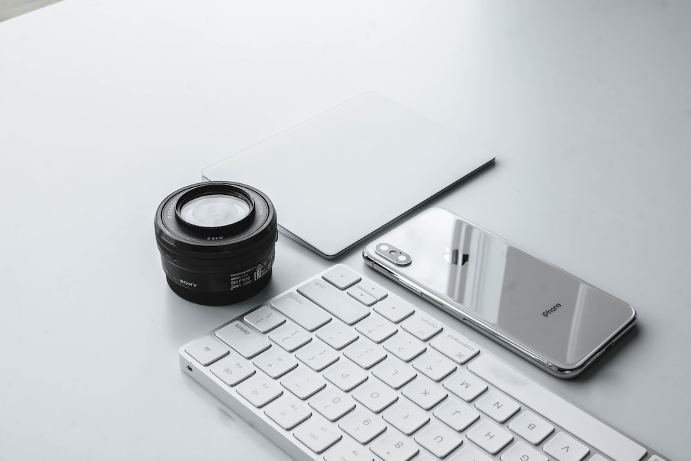 silver iPhone X beside camera lens and Apple Keyboard