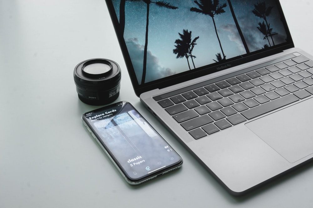turned-on MacBook Pro beside black smartphone on gray surface