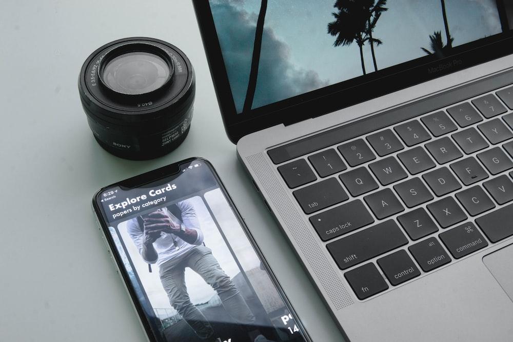 black phone beside MacBook Pro