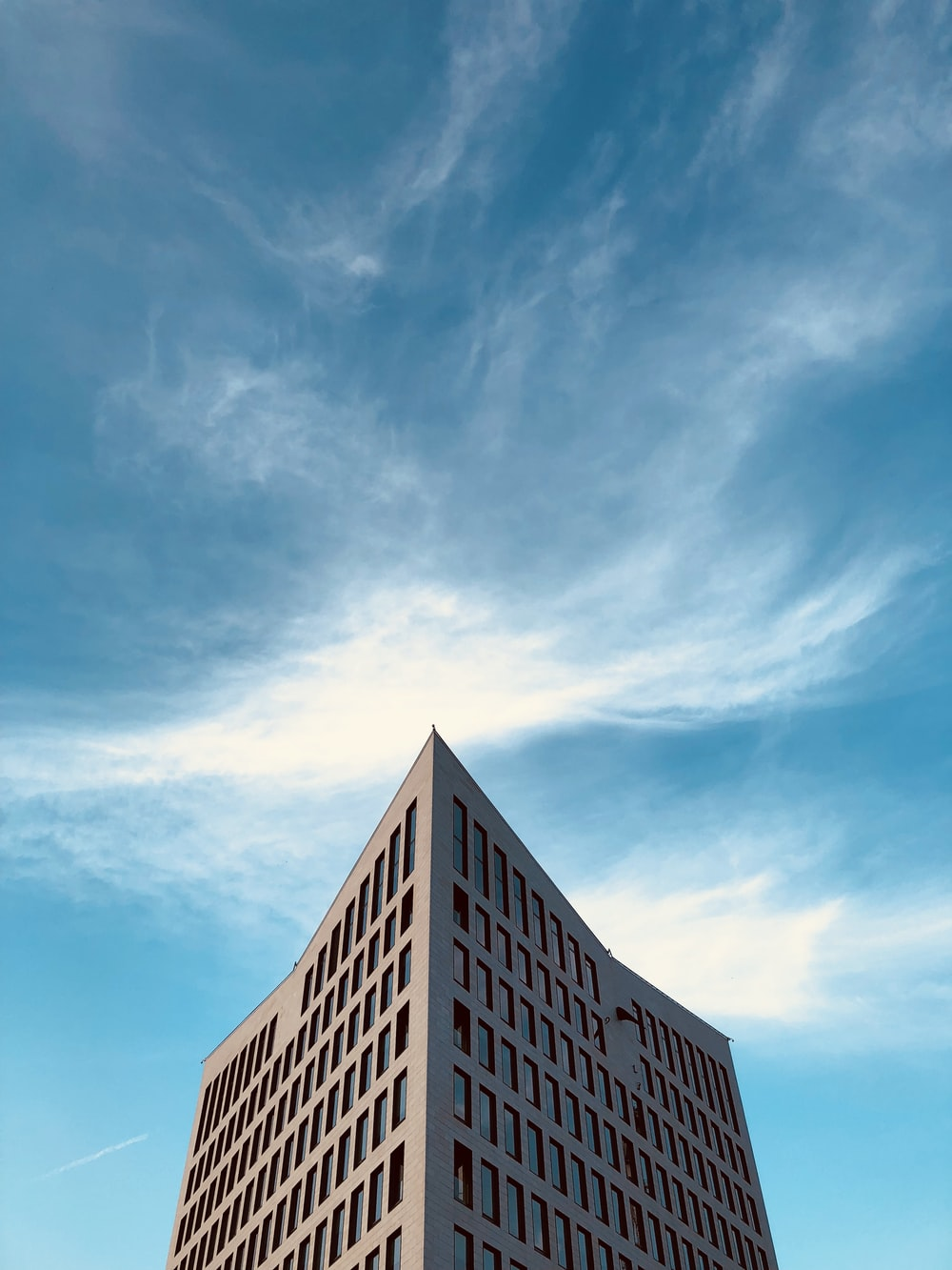 low-angle photography of high rise building under white clouds at daytime