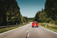 red Volkswagen Beetle travelling on road near trees during daytime