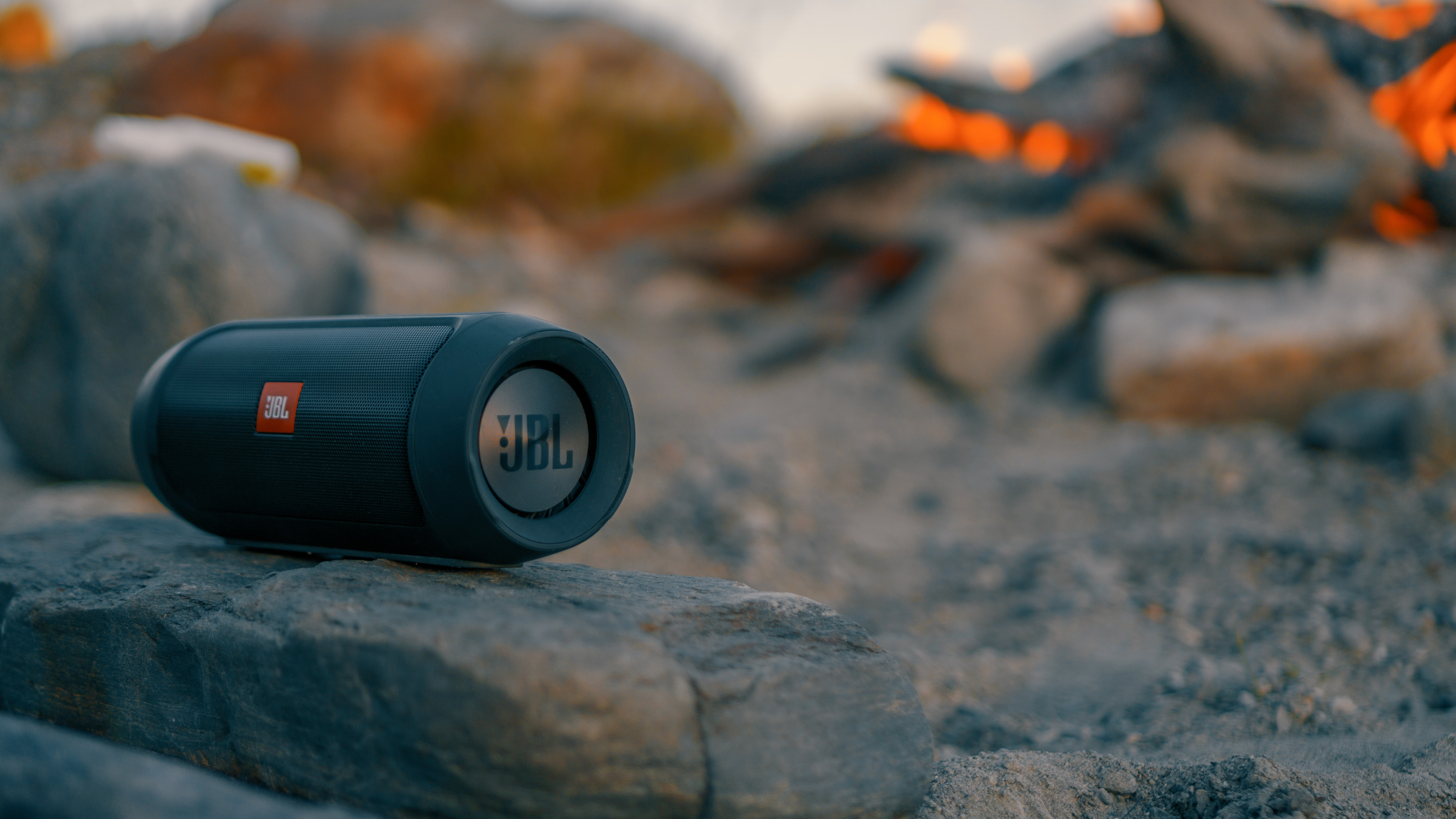 selective focus photography of JBL Charge portable speaker on gray stone