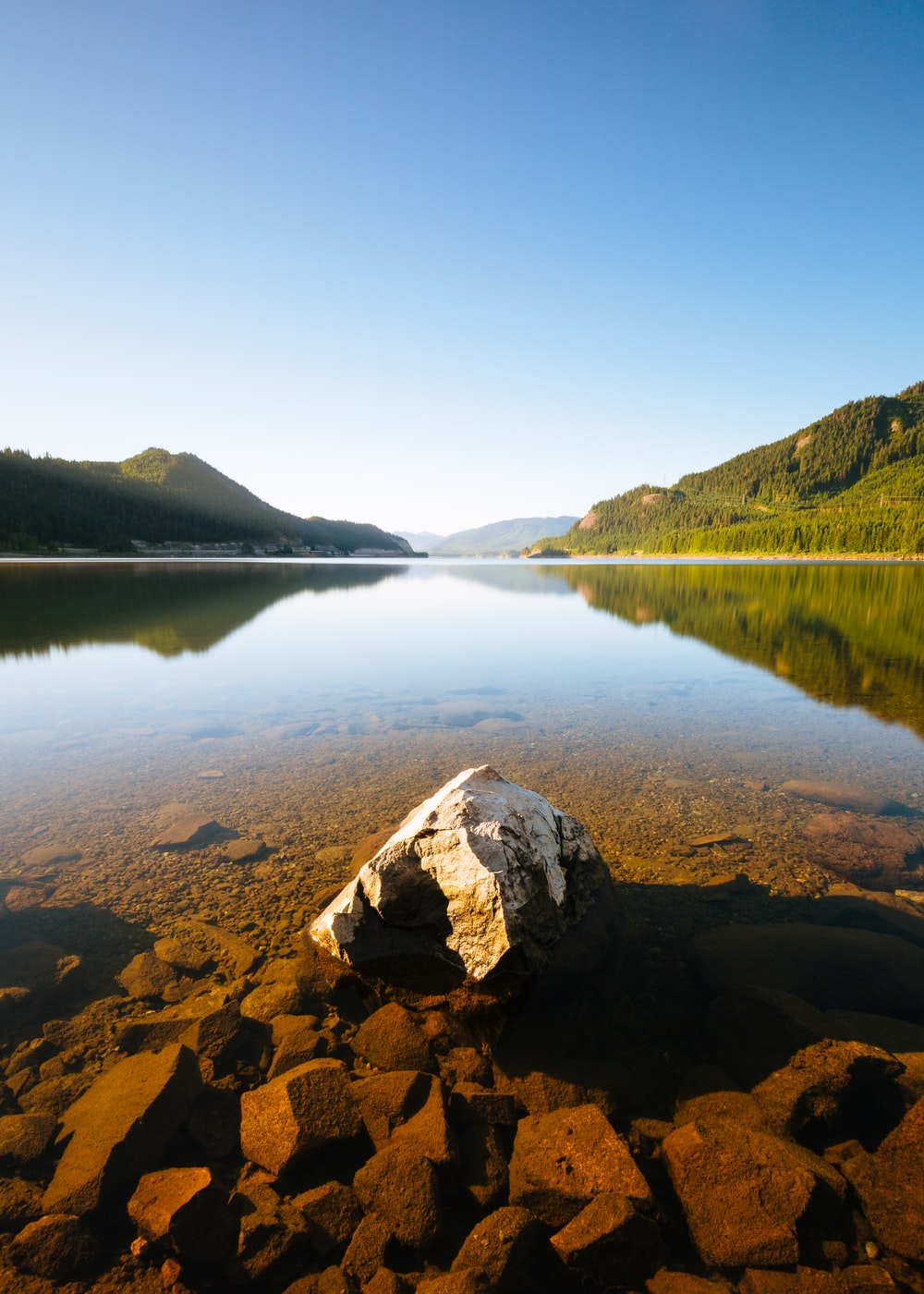 photo of calm body of water between mountain
