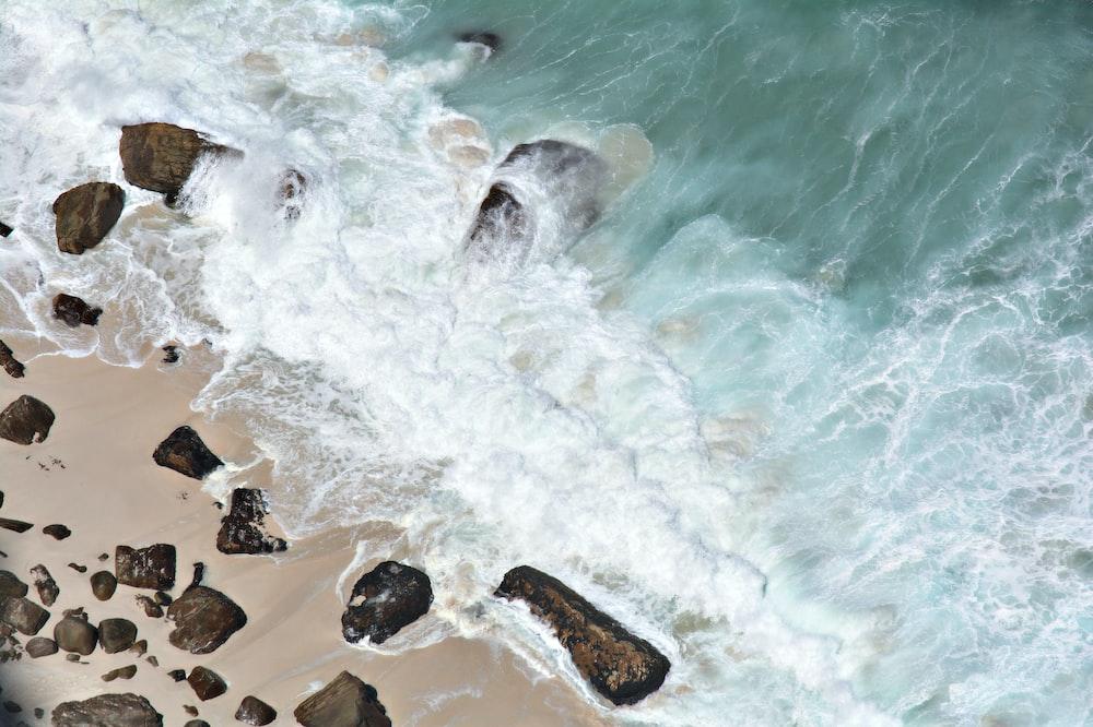 body of water splashing in a rock