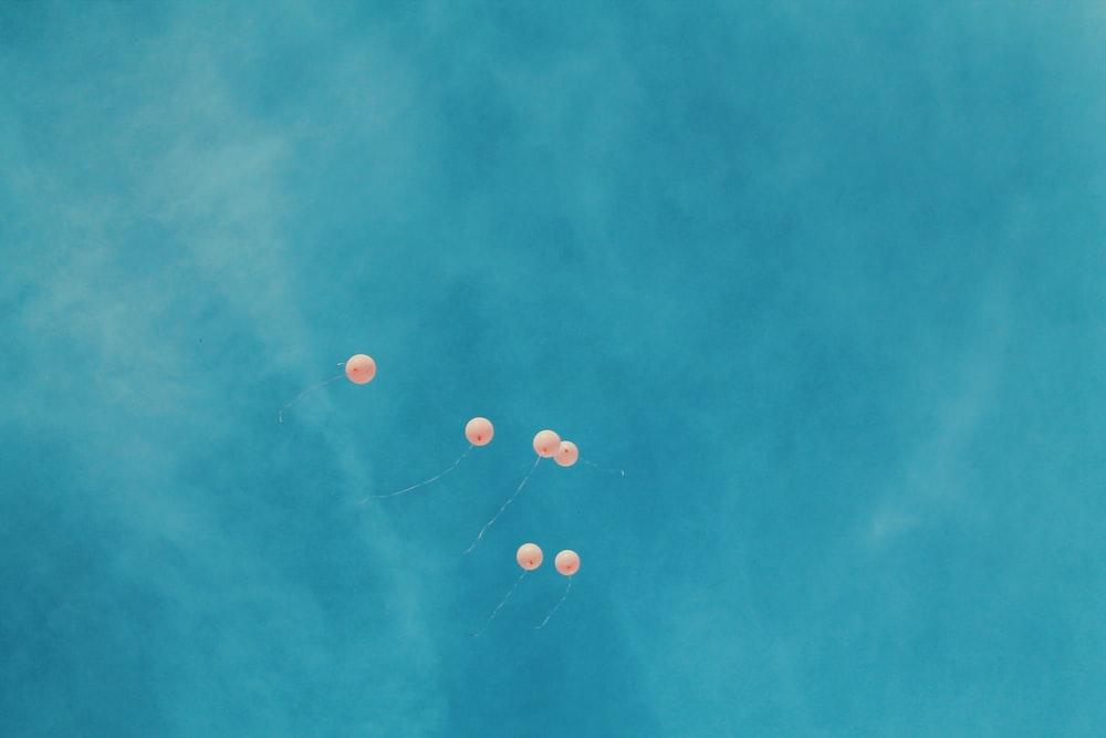 low angle view of six orange balloons during blue sky