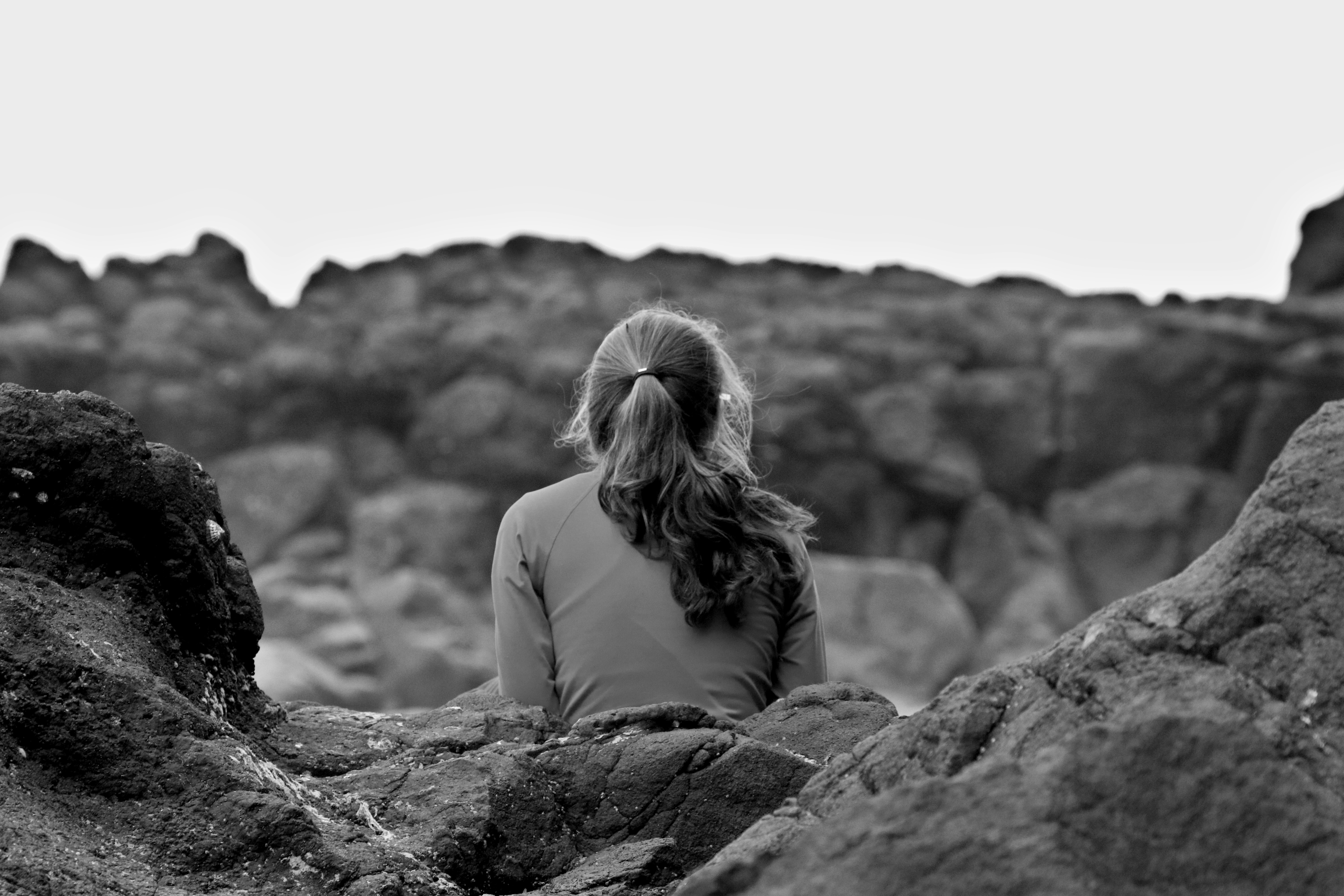 grayscale photography of woman sitting on rock