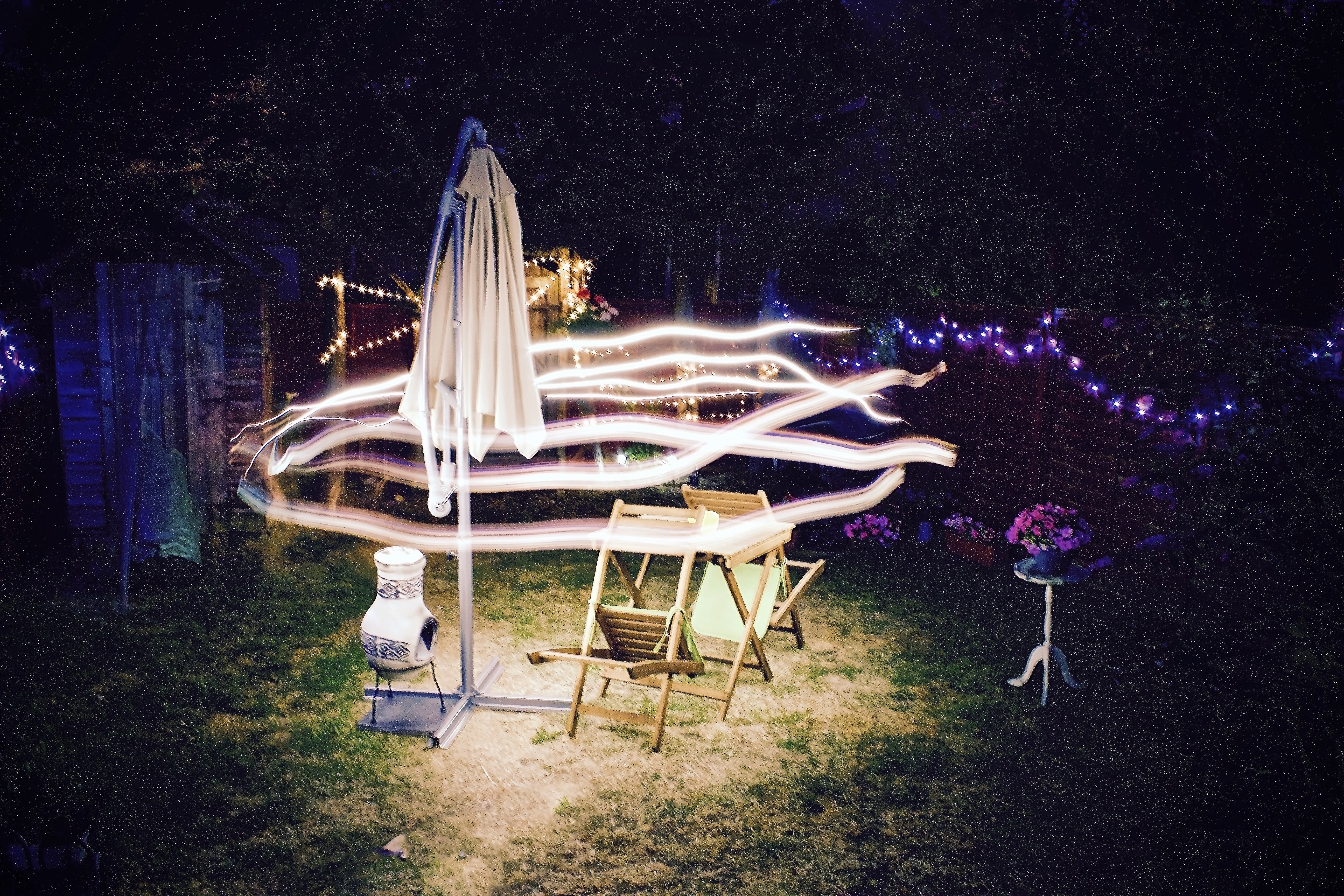 time lapse photography of lights over cantilever parasol and folding chairs at nighttime
