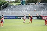 photo of woman kicking soccer ball