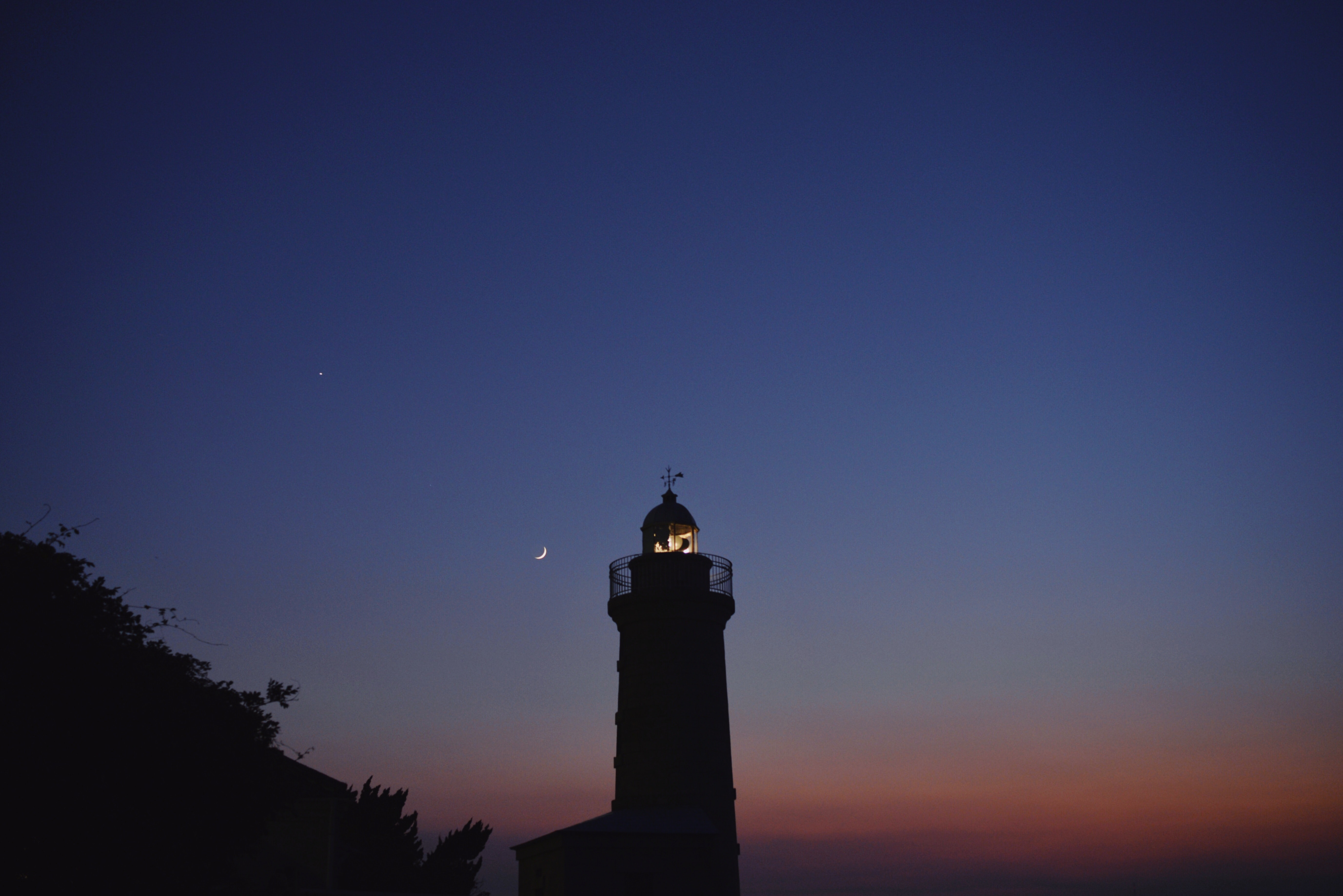 silhouette of lighthouse during nighttime