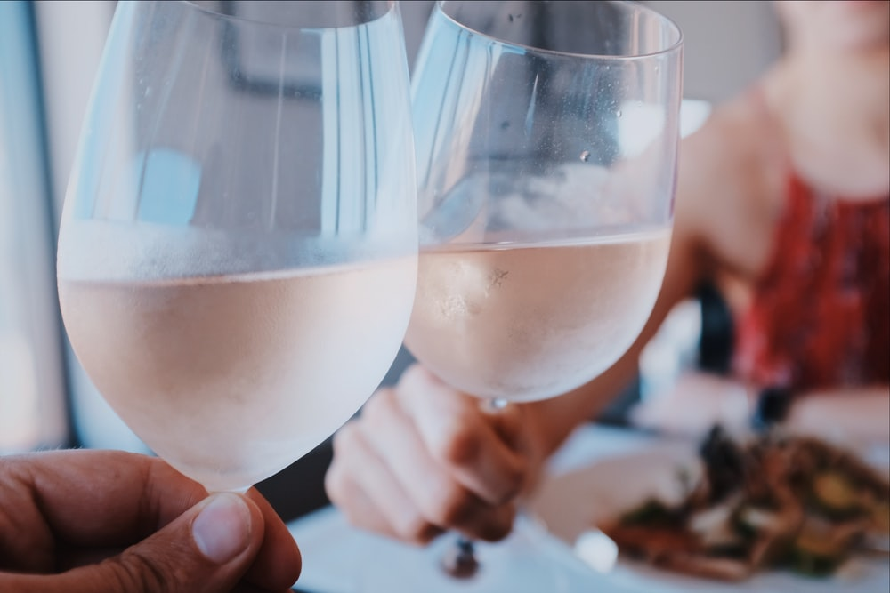 two person toasting wine glass cups