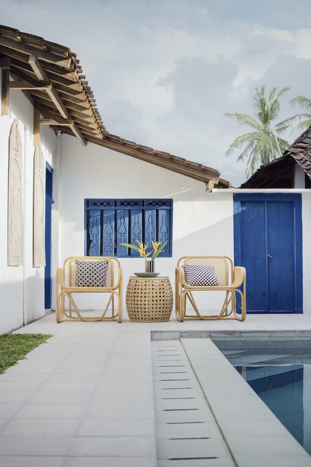 wicker table and two chairs near swimming pool