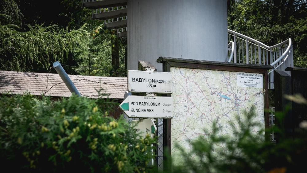 white road sign near brown wooden door
