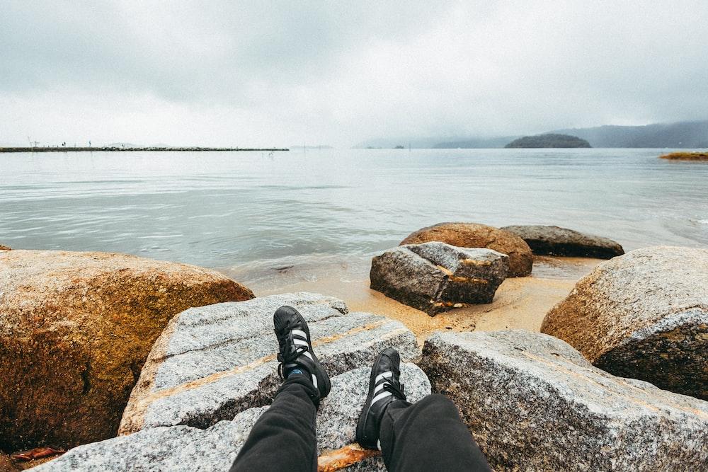 man sitting on gray stone beside the seashoee