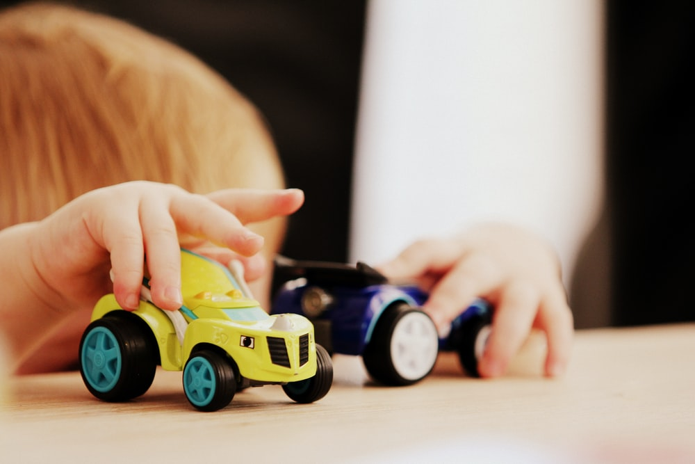 child playing with two assorted-color car plastic toys on brown wooden table