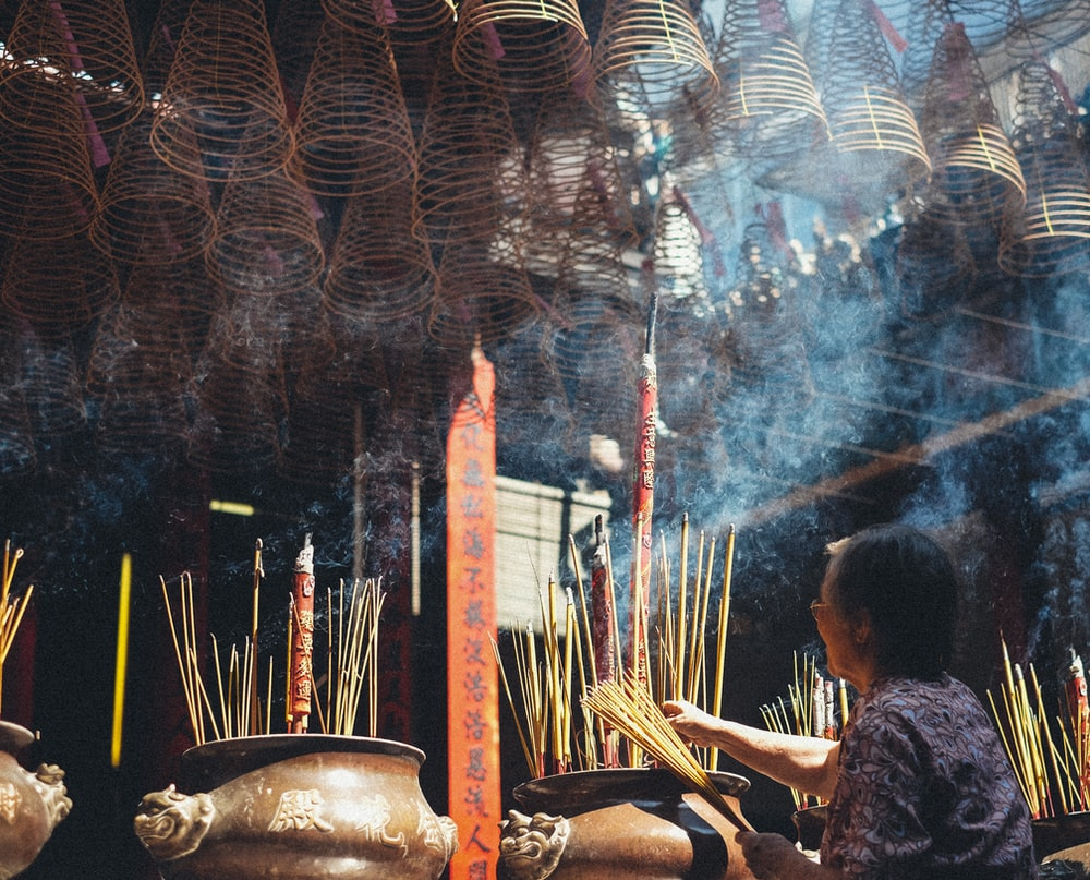woman holding brown incense sticks