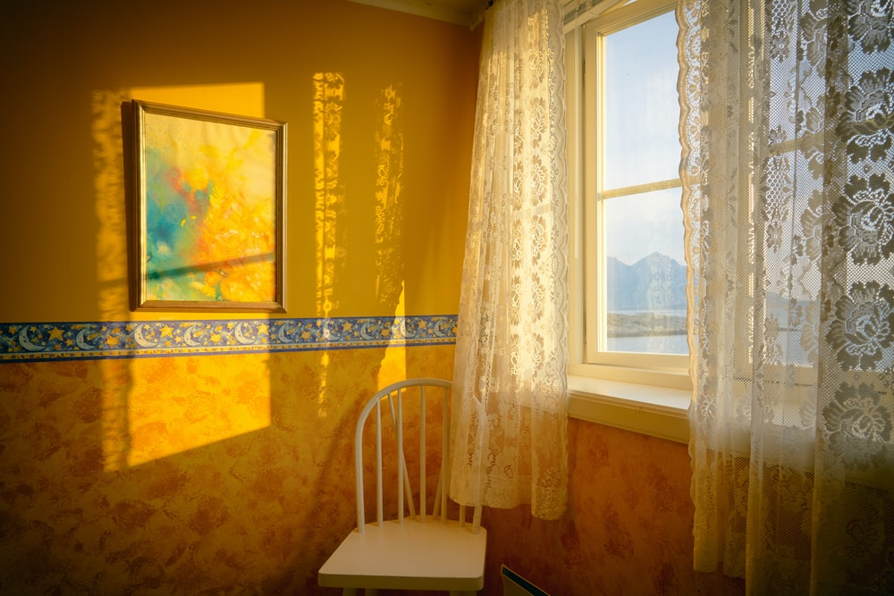 white chair placed beside window with curtain