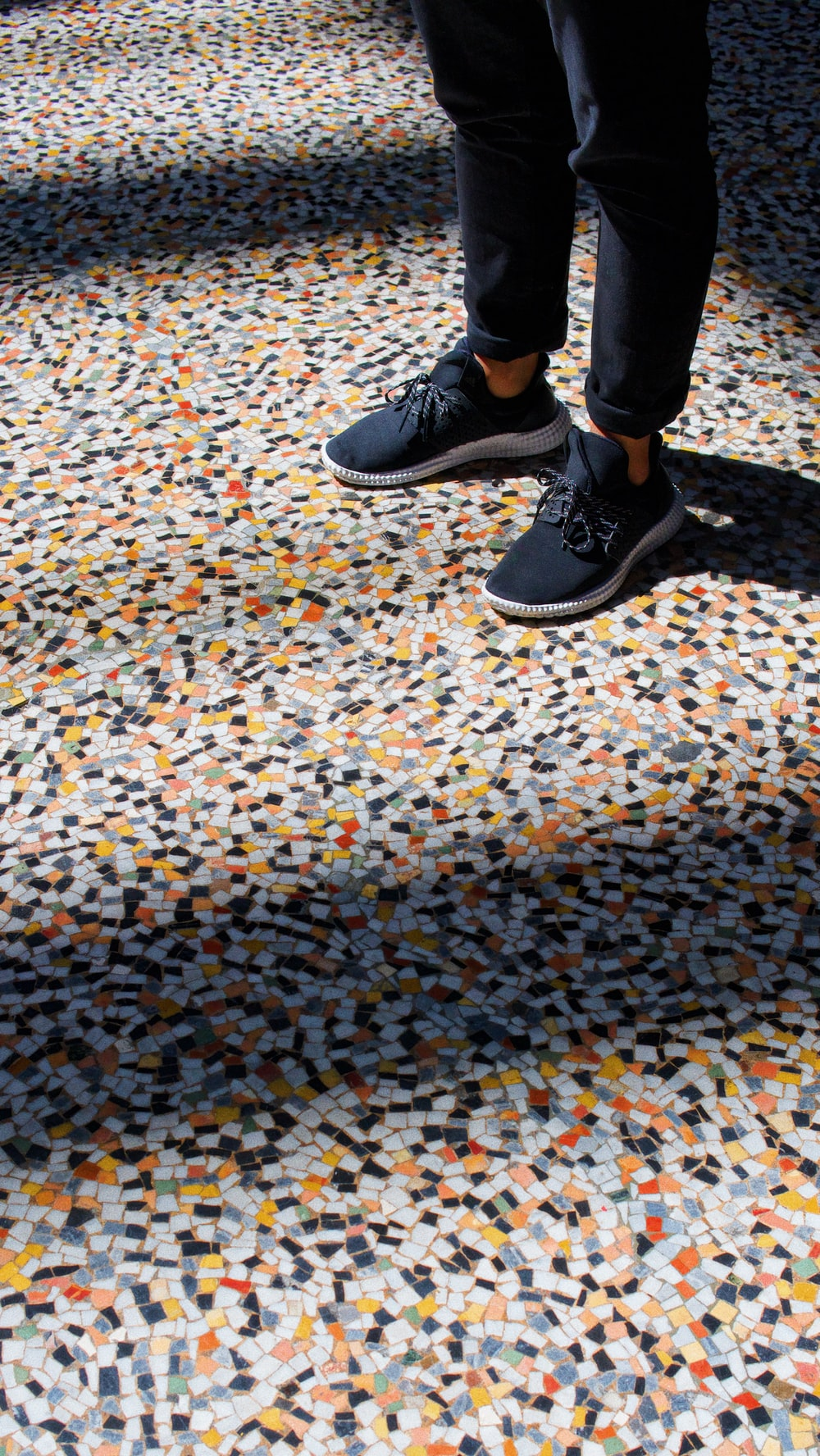 person standing on multicolored tiles