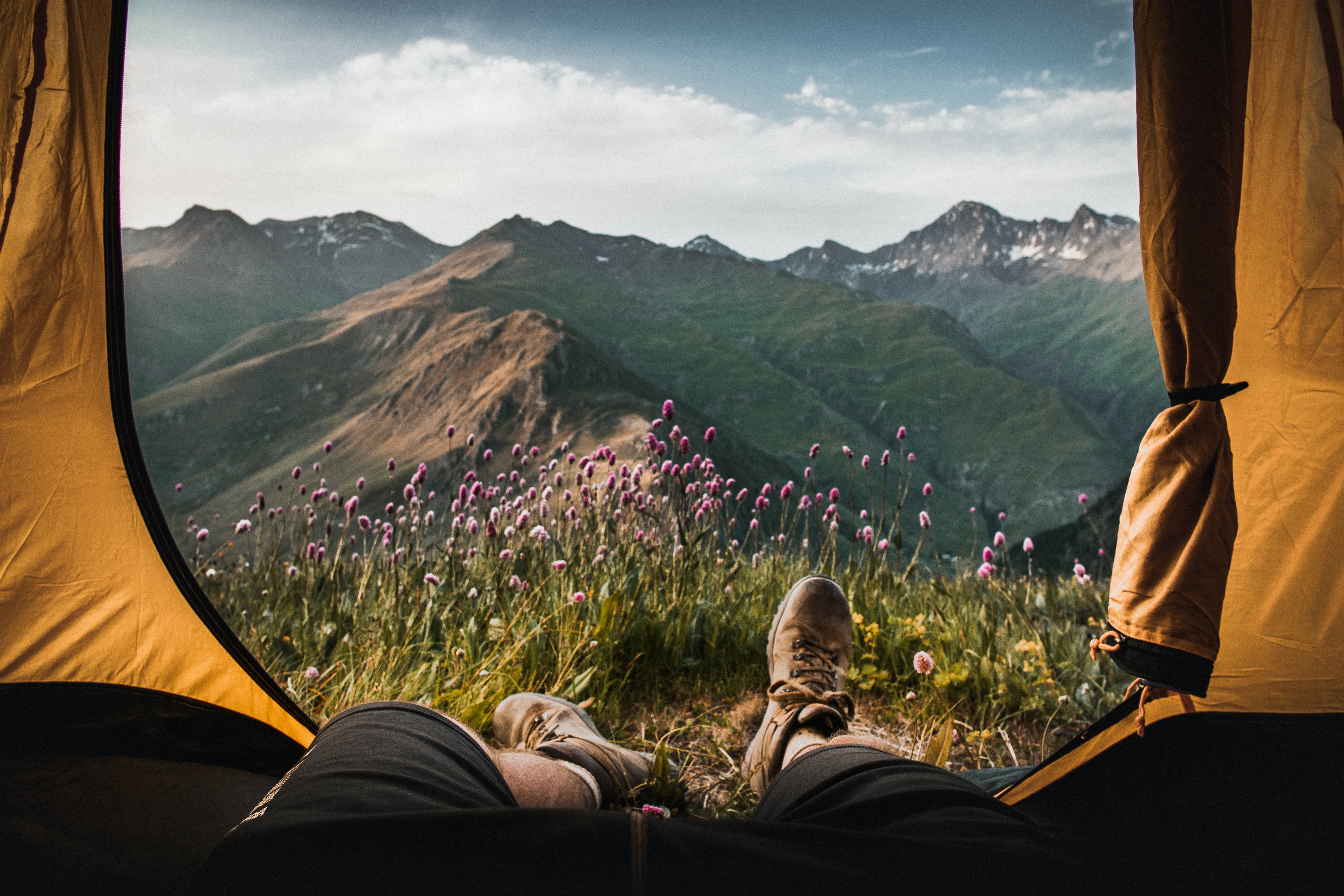 person lying inside tent and overlooking mountain