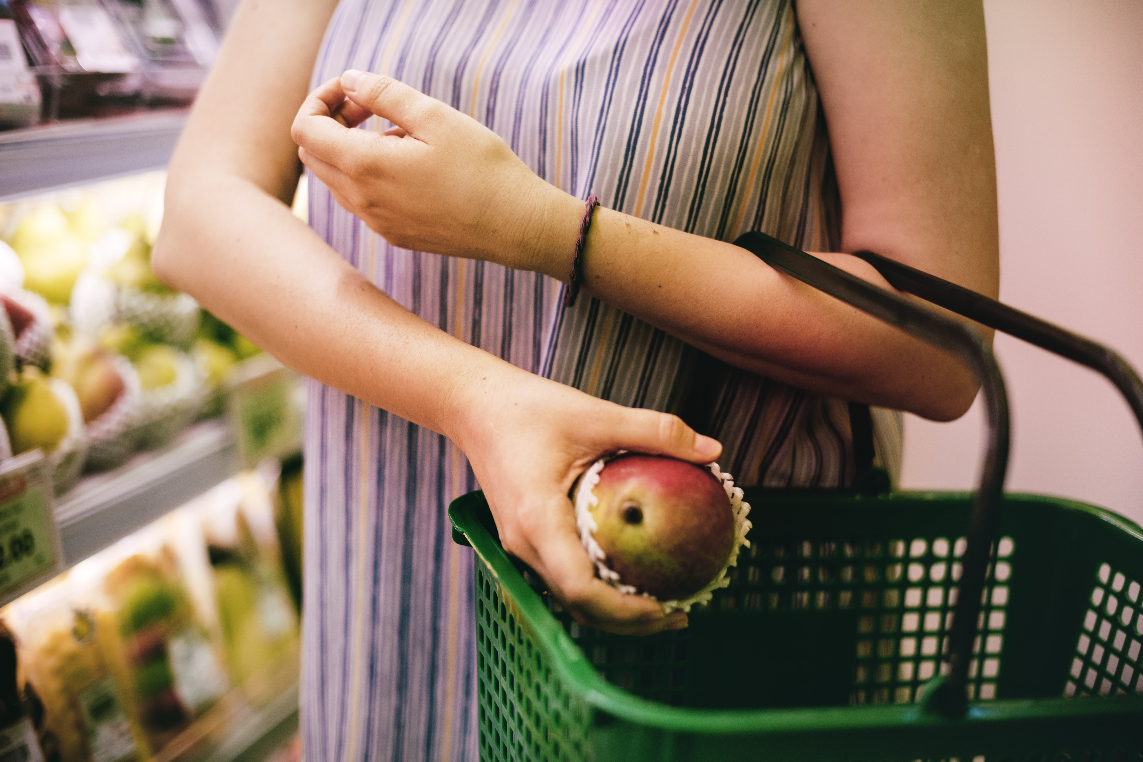 woman carrying green basket while holding fruit