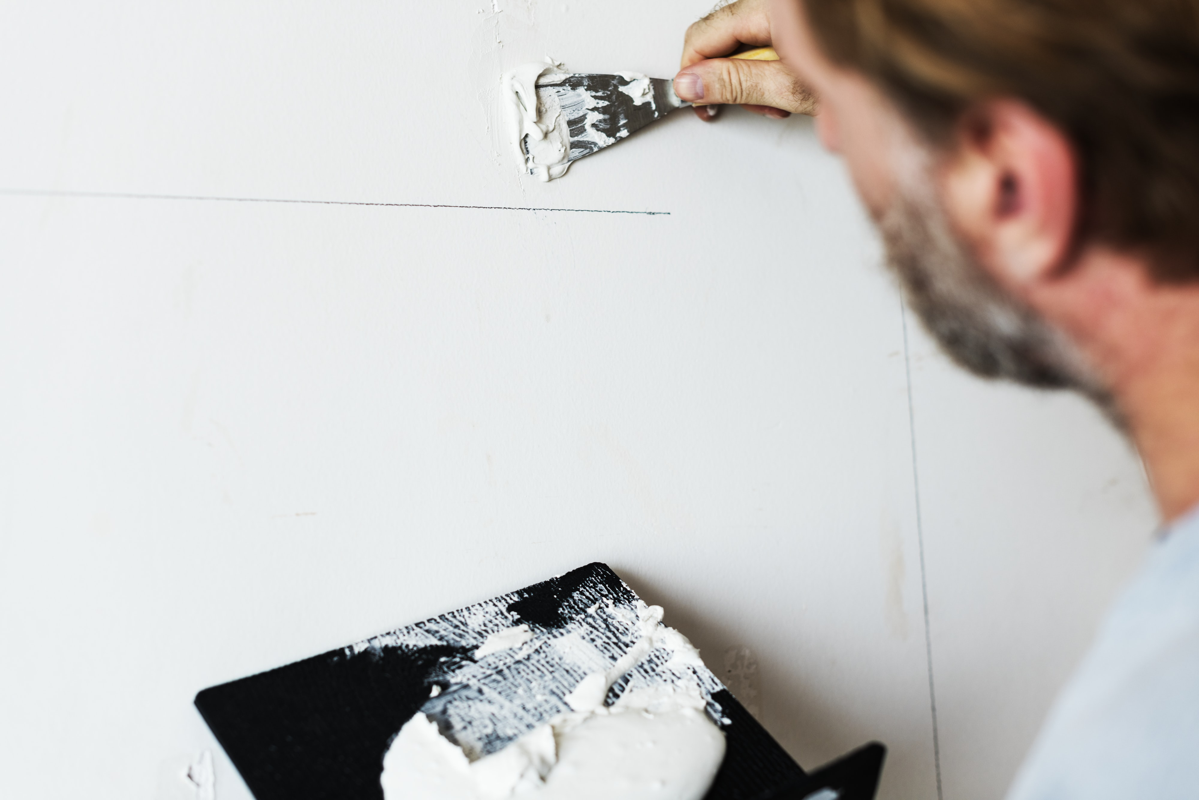 person putting white paste on wall