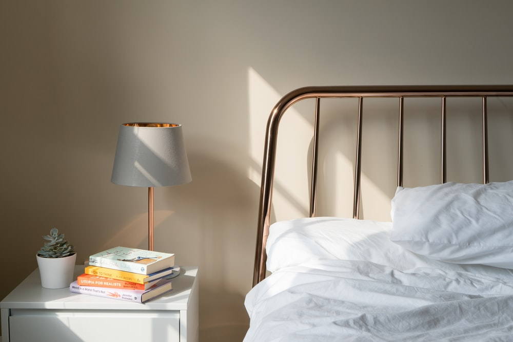 table lamp on white wooden nightstand beside bed