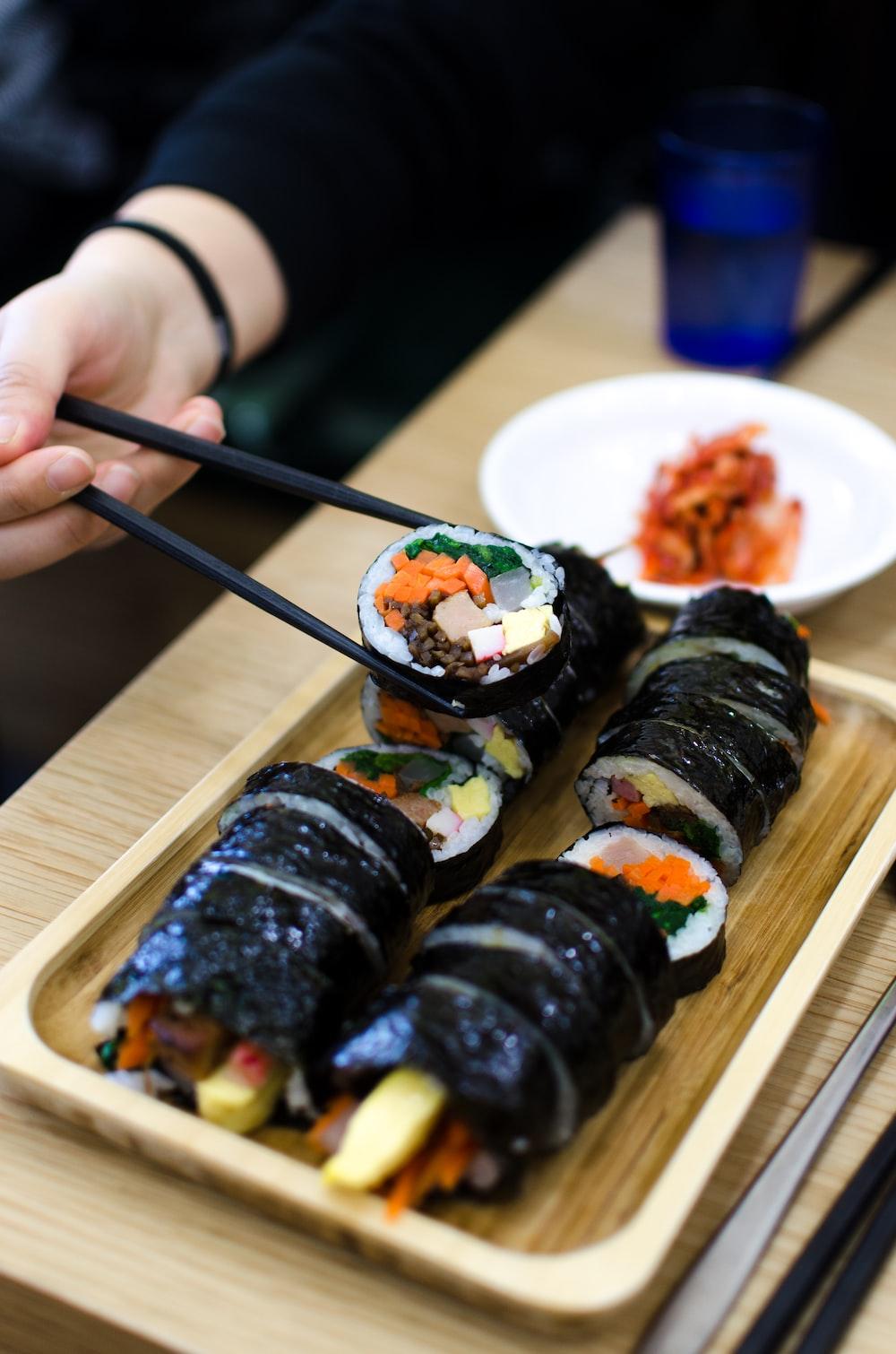 person picking sushi using chopsticks