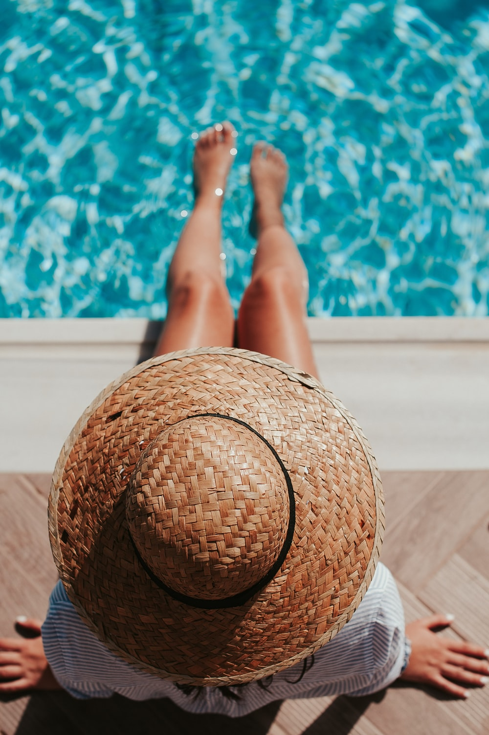 woman sitting on poolside setting both of her feet on pool