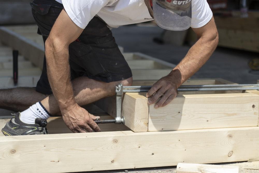 man holding gray metal hand tool