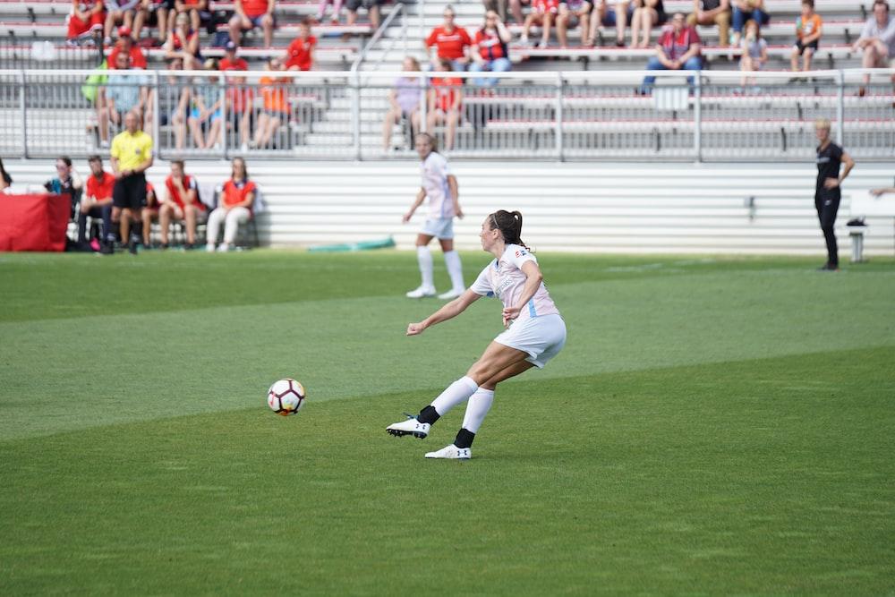 women athletes playing soccer during daytime