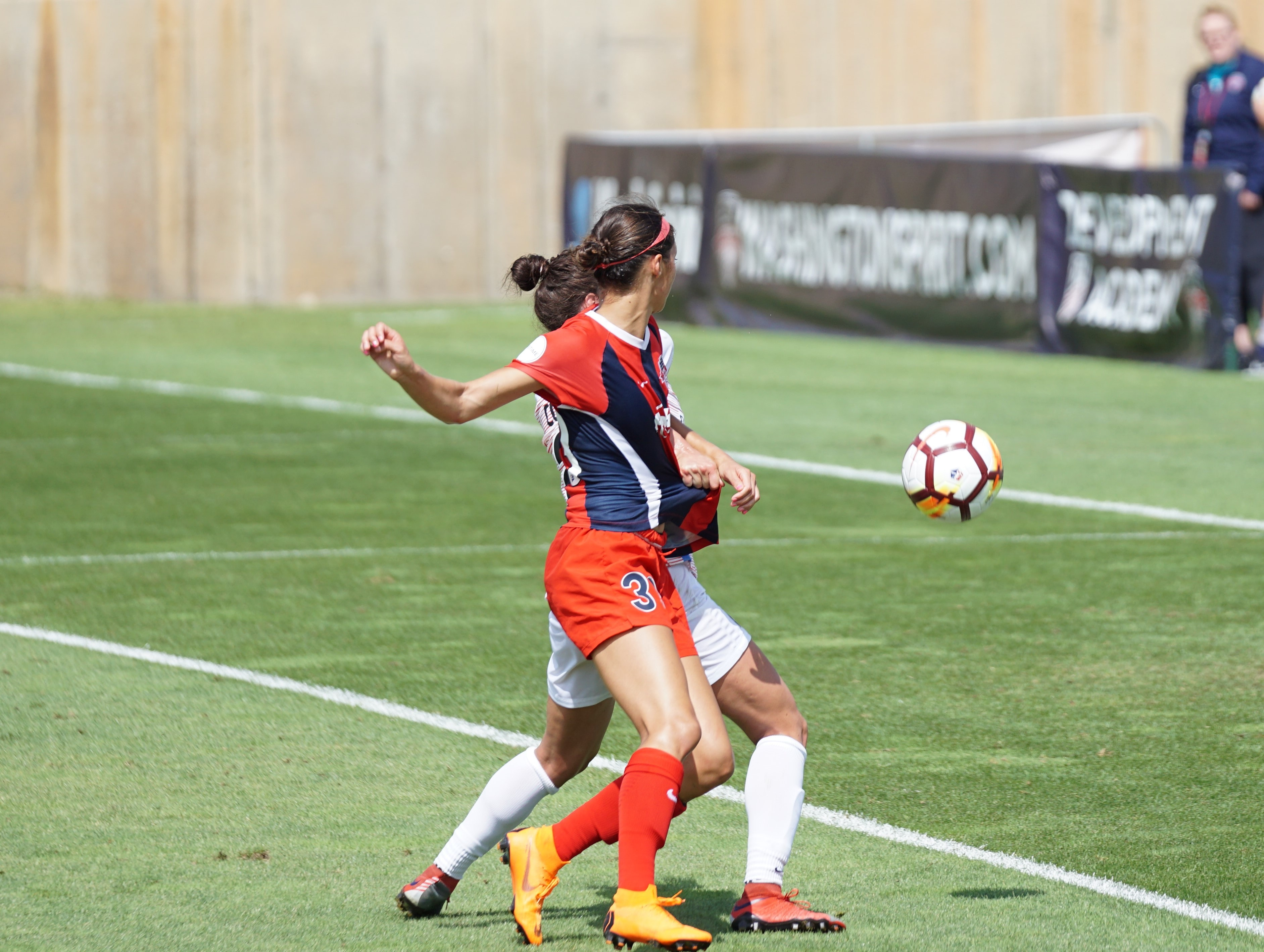 two women soccer player standing on soccer field at daytime