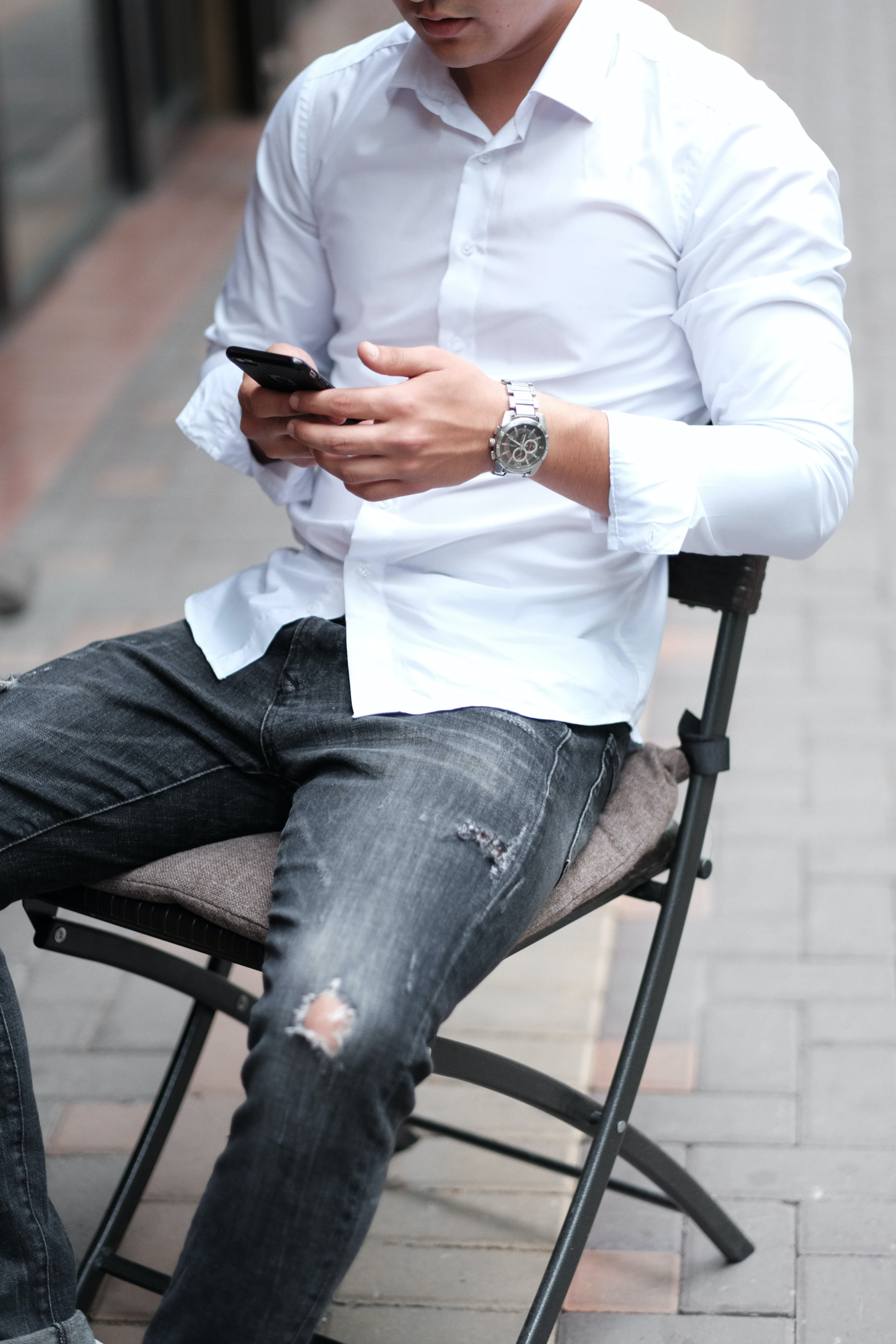 man sitting on chair while holding smartphone